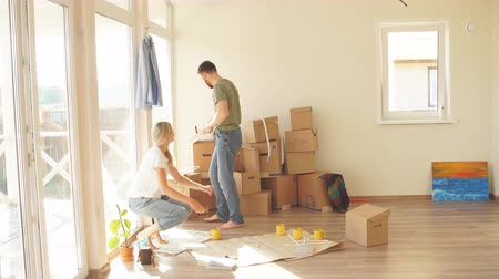zkoumat : Young couple sitting at floor moving into new home looking at floor plans together