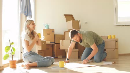 межрасовый : Portrait of happy caucsian couple planning new house design looking at paper
