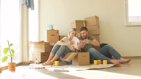 em branco : Couple sitting on floor reading book with boxes in the living room. Moving house couple relax lifestyle at home concept