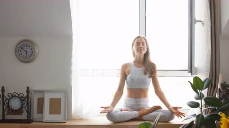 restorative : Female yoga teacher greets at the begining of practicing yoga exercise, namaste, working out, wearing sportswear, white t-shirt, leggings, studio isolated shot against white wall