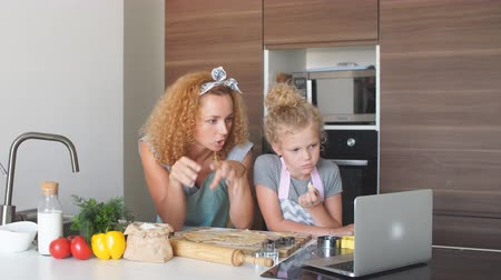 bodorítás : happy loving mother helps her daughter with her on line homework at home, using laptop. Technology and Education Caucasian Blonde Family concept Stock mozgókép