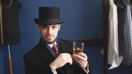 хорошо : Handsome young man in a classic suit drinking whiskey.