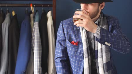 формальный : Elegant man in fashion checkered suit and hat posing at atelier with beverage in hand , clothes rack with ready made mans suits on background