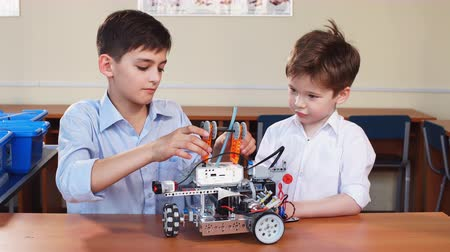 öğrenme : Two little curious technicians of various ages playing with robotic car toy at at a robot performance demonstration. Stok Video