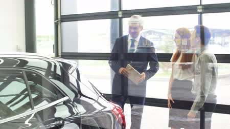 car dealership : Couple is talking to mature sales manager while choosing a car in dealership Stock Footage