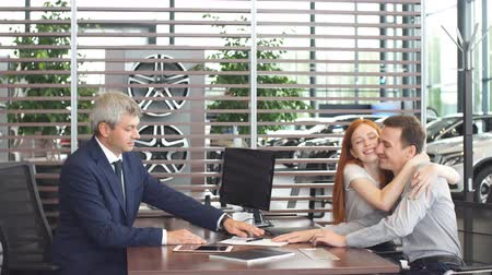 буклет : Agreement or contract concept. Confident mature salesman or manager offering car purchase contract to young couple.