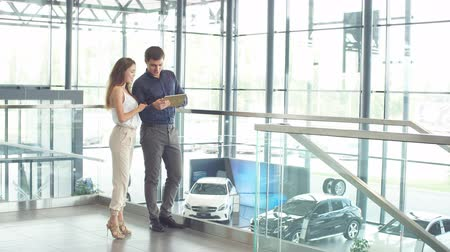 буклет : Attractive young couple of european appearance reading a booklet at the dealership showroom choosing a car.