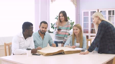 front cover : Handsome Arabian young bearded man surrounded by multiracial male and female students holding in hands big ancient book in library Stock Footage