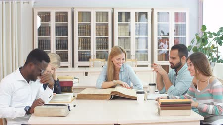 reference : Multiethnic young people sitting at table reading big old reference book for preparing scientific report. Group of young students doing together homework at library. Stock Footage
