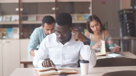 acessibilidade : Young African male manager wearing white shirt continued his education in the USA university studying marketing management in the business development department. Vídeos
