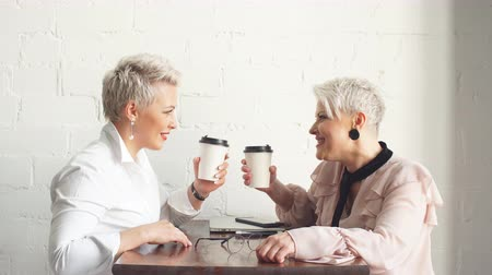 cooperar : Two female senior collegues sitting next to each other in cafe