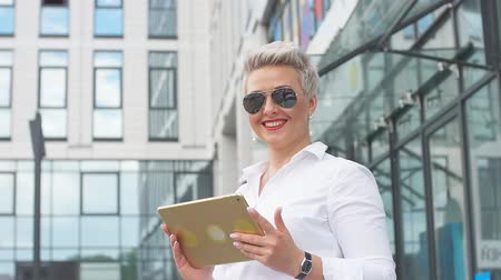 スイート : Happy business woman wearing white suite and sunglasses using tablet pc in front of office building