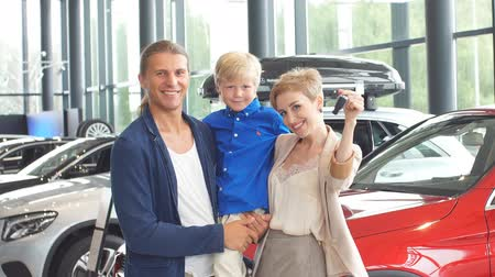 sprzedawca : Happy family near new car. Auto dealership centre.