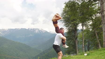 squat : Athletic woman doing single leg split squat exercise with her male partner outdoors over high mountains in background