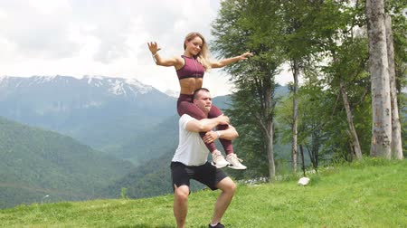 quads : Athletic woman doing exercise with her male partner outdoors over high mountains in background
