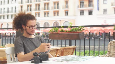 viajero : Young guy traveler planning trip for vacation with smartphone and map while sitting at cafe. Slow motion Archivo de Video