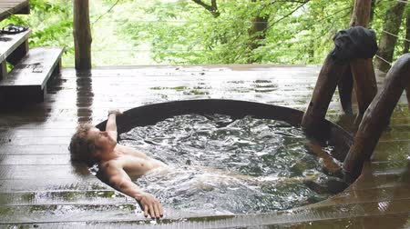 джакузи : attractive young man with curly, fair hair is relaxing in the cold ooden tub after bathhouse. relaxation concept