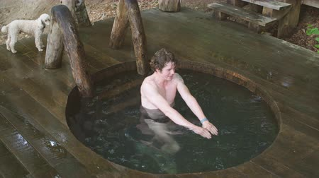 джакузи : young attractive awesome man is testing new wooden bathtub which is situated in the forest. Стоковые видеозаписи