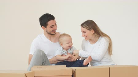 ипотека : Happy family moving in new house. smiling boy help parents and carrying moving boxes on foreground