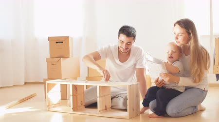 vidalar : family with little boy reading instruction and assemble furniture together at living room of new apartment pile of moving boxes on background Stok Video
