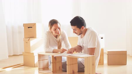 instruções : couple reads instructions for Assembly of furniture in new house with moving boxes on background