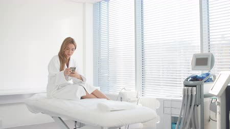 kozmetikus : Good looking female client of spa beauty clinic, sits in white bath robe, demonstartes healthy skin, long hair, natural beauty, going to have spa treatment. Skin care