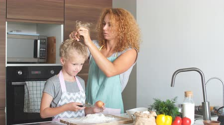 kıvırcık saçlar : Caucasian mother and cute little daughter having fun in the kitchen while mother puts daughter frizzy fair hair back, the girl looking at camera Stok Video