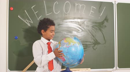 notas : african american Boy with a globe on study table on chalk board background