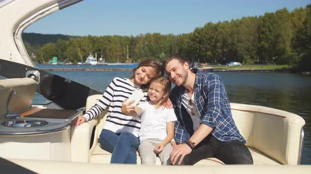 affluent : Family spends time together by the lake in autumn. The family uses a smartphone for selfies. Autumn weekend in the open air by boat.