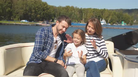 affluent : The family spends time together by the lake in autumn. The family uses a smartphone to navigate their route. Autumn weekend in the open air by boat.