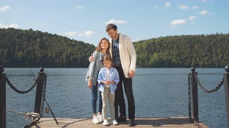posou : Portrait of Happy Family looking at camera while posing on pier at quiet lake Vídeos