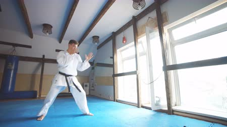 legs only : Karate. Man in kimono doing high kick with his foot Stock Footage