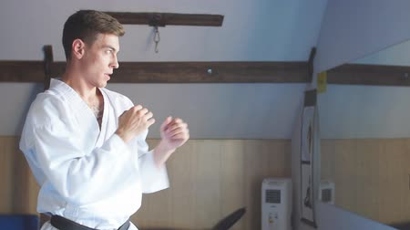 tanítvány : Caucasian Man in white kimono with black belt training karate in gym. Slow motion