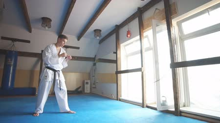 legs only : Karate. Man in kimono doing high kick with his foot. Slow motion
