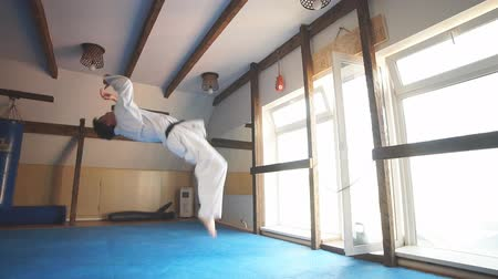каратэ : Caucasian Man in white kimono with black belt training karate in gym. Slow motion