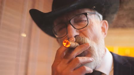 связать : Aged old-aged male wearing optical glasses and big hat, dressed in dark blue elegant three piece suit smoking a cigar looking at camera with pensive look on his wrinkled face