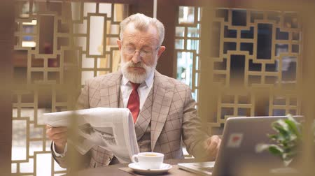 jornal : Indoor portrait of a confident and handsome business mature European man wearing spectacles, looking at newspaper laptop holding a cup of coffee while sitting at a table with laptop in a cafe