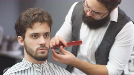 beard trimming : Working process in modern barbershop. Male hairdresser serving client, making haircut using metal scissors and comb, both looking at camera