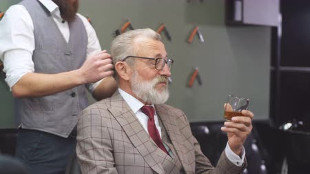 sur mesure : Professional young barber giving a haircut with concentration to a rich respectable gentleman, standing and holding razor while relaxed elderly client is smoking cigar and drinking alcohol.