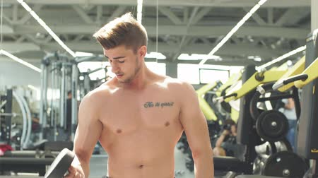 kulturystyka : Tough caucasian young guy lifting weights in modern gym, sport lifestyle indoors, Power and Man s beauty Wideo