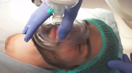 operation theater : Anesthesiologist gives mask inhalation anesthesia to a male caucasian patient
