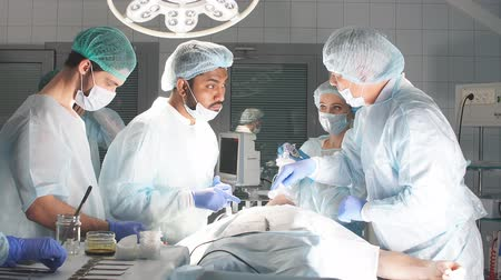 surgical instrument : Concentrated Surgical team operating a patient in an operation theater. Well-trained anesthesiologist with years of training with complex machines follows the patient throughout the surgery. Stock Footage