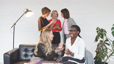 meeting negotiate : Smiling african woman looks at photos on tablet, her girlfriend sharing with her, sits on the sofa, while other women stand on background. People, technology, partnership