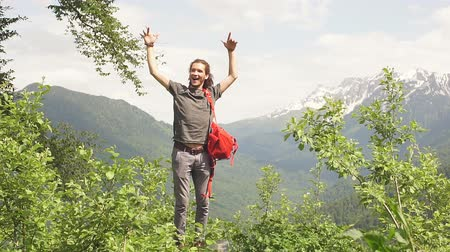 podróżnik : Traveler Man with backpack raised hands. mountains landscape on background Lifestyle Travel, happy, emotions, success concept. Slow motion