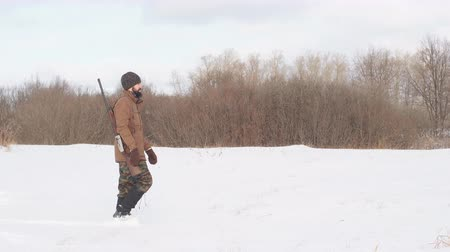 karabély : Male warm clothes walking on the field with hunting rifle. interest, lifestyle. Stock mozgókép