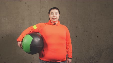 xxl : pleasant overweight woman with exercise ball isolated on gray background. sport, fitness, lifestyle Stock Footage