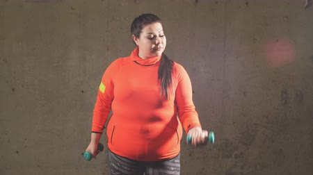 xxl : Young plump female bodybuilder is training with dumbbells in the sport center. free time. lifestyle