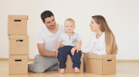 rodzeństwo : Family, parents and son, unpacking boxes and moving into new home, baby help for parents
