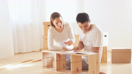 yapıştırma : Young couple installing furniture in new house with instruction