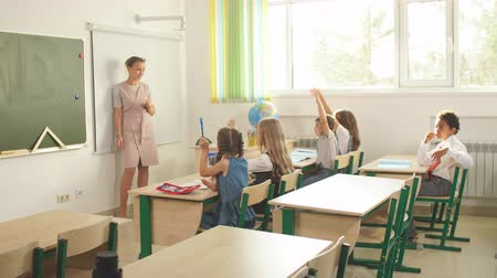 özel öğretmen : Female teacher teaching schoolchildren using board in classroom